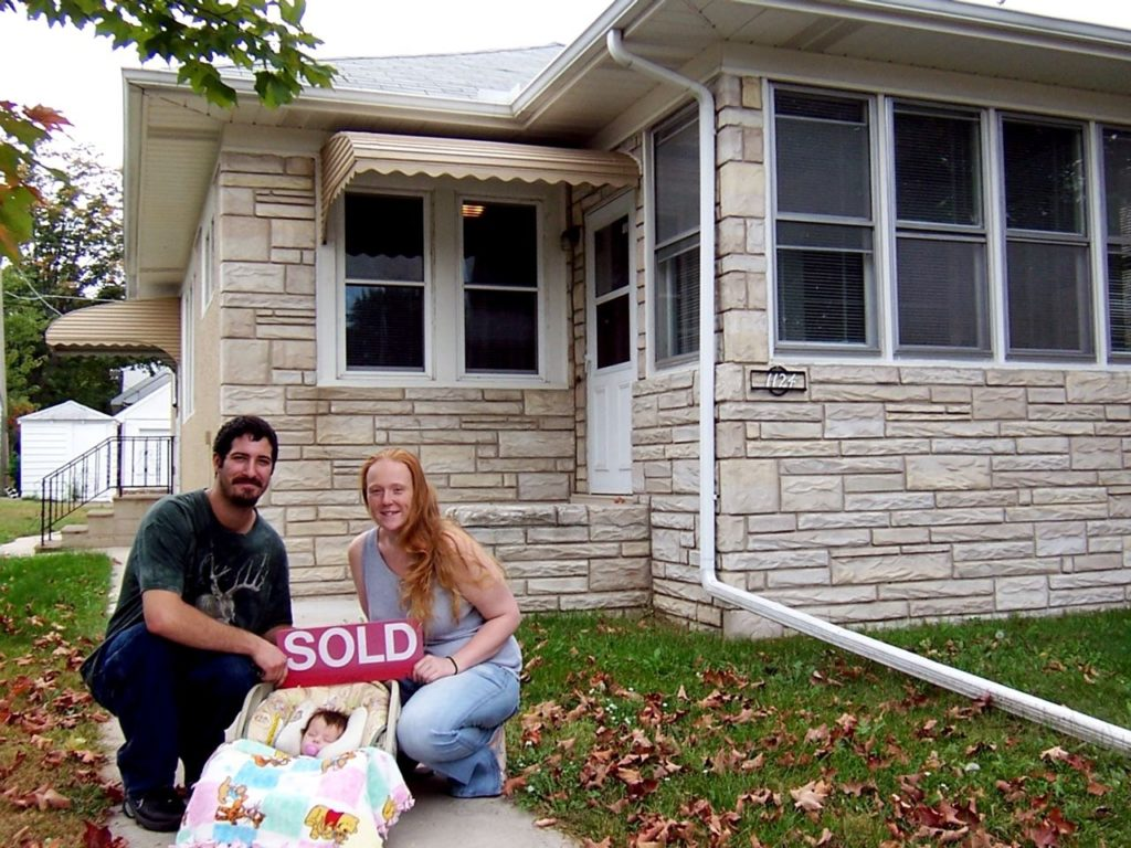 "A couple and their baby hold a ""sold"" sign in front of their new home. NWHP helps people improve their credit so they can qualify for better mortgage rates."