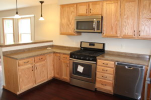 A new kitchen with oak cabinets and stainless appliances.