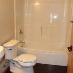 A new all-white bathroom with dark vinyl flooring.