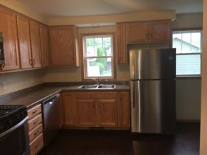 A new home's kitchen, with oak cabinets and stainless appliances.