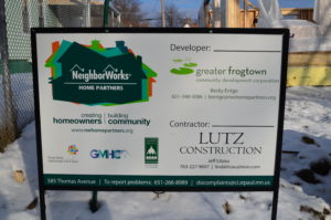 A NeighborWorks Home Partners yard sign with a property under construction in the background.