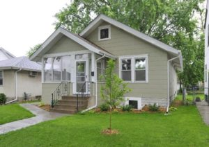 A home rehabbed by NeighborWorks. It is a one-story bungalow style with taupe siding and a newly-planted magnolia tree in the front yard.