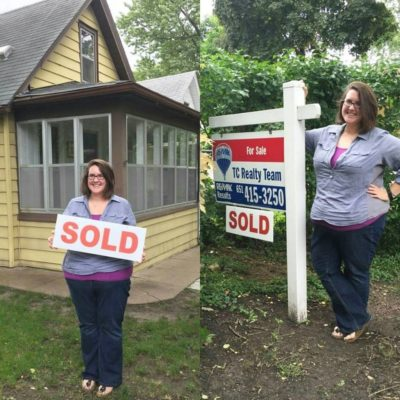 "A woman stands in front of her new home holding the ""sold"" sign."