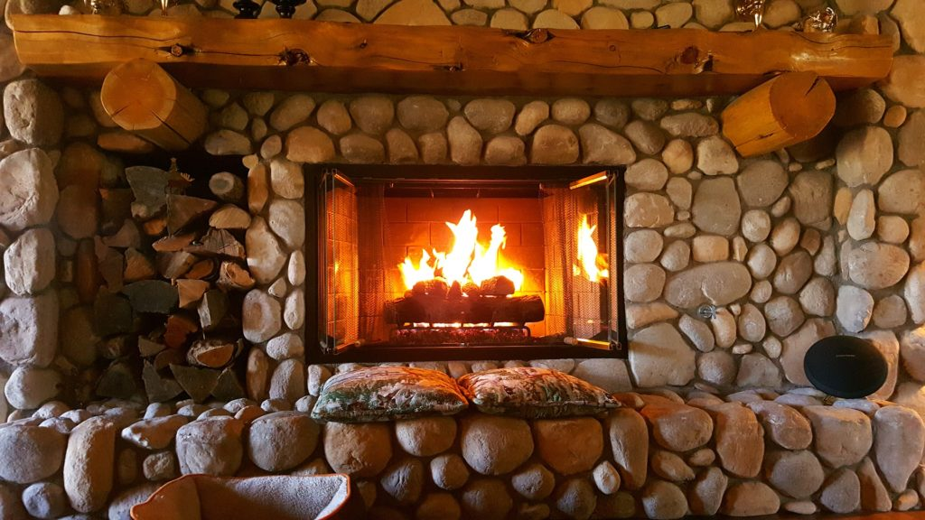 A fire burns in a fieldstone fireplace.