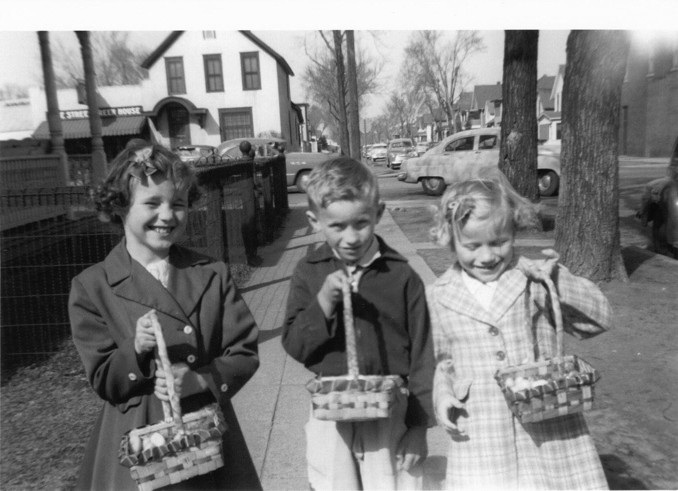 Neighborhood children show their Easter baskets in 1956. The Dale Street Greenhouse is in the background.