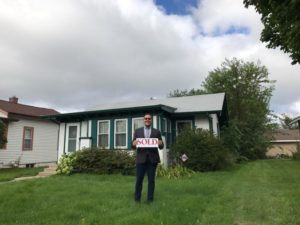 "a new homeowner stands in front of his home holding a ""sold"" sign"