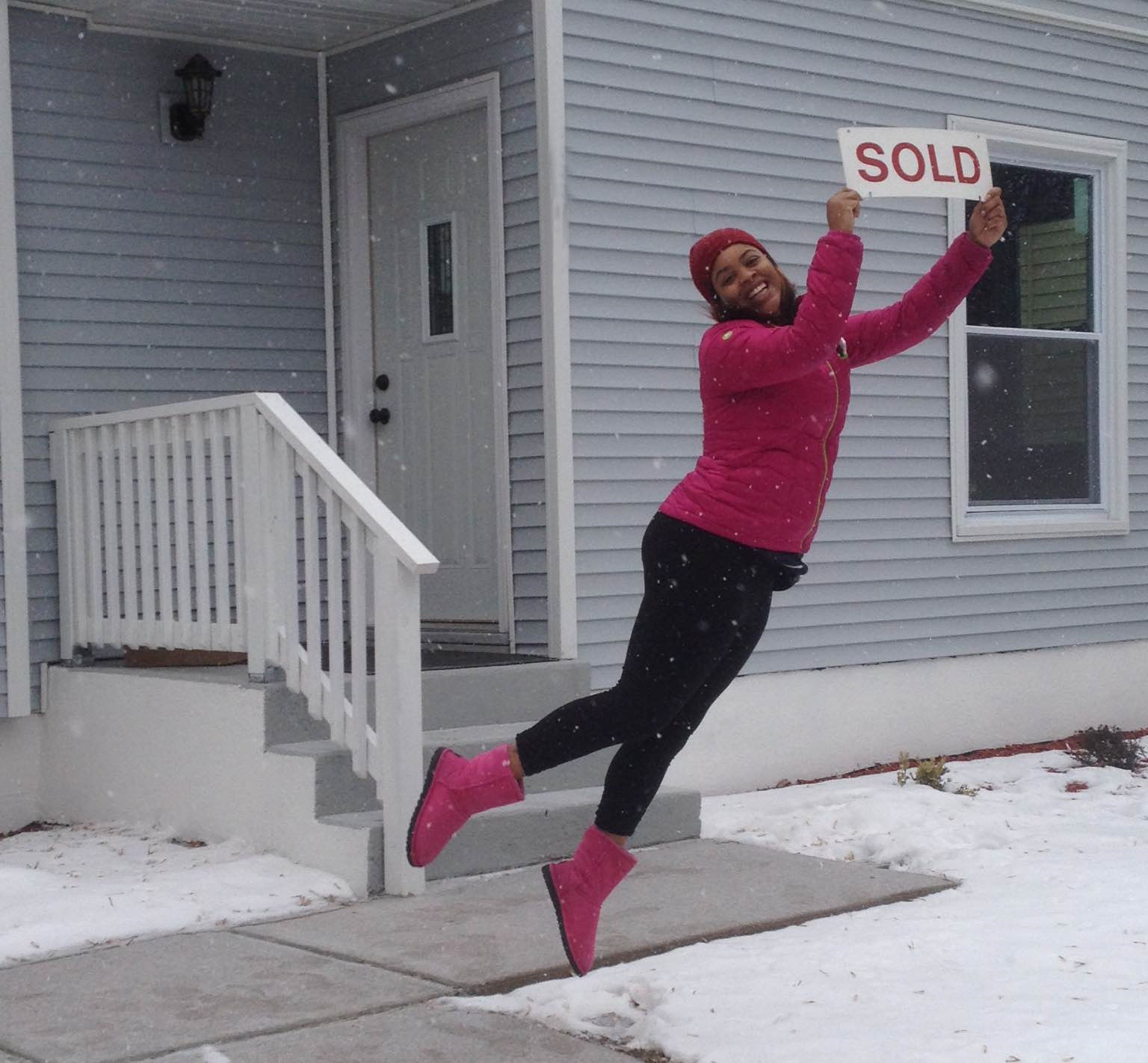 a happy new homeowner leaps into the air at her new home