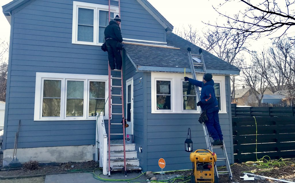 Two workers on ladders add trim to a Saint Paul house that has had new siding installed with home improvement funds.