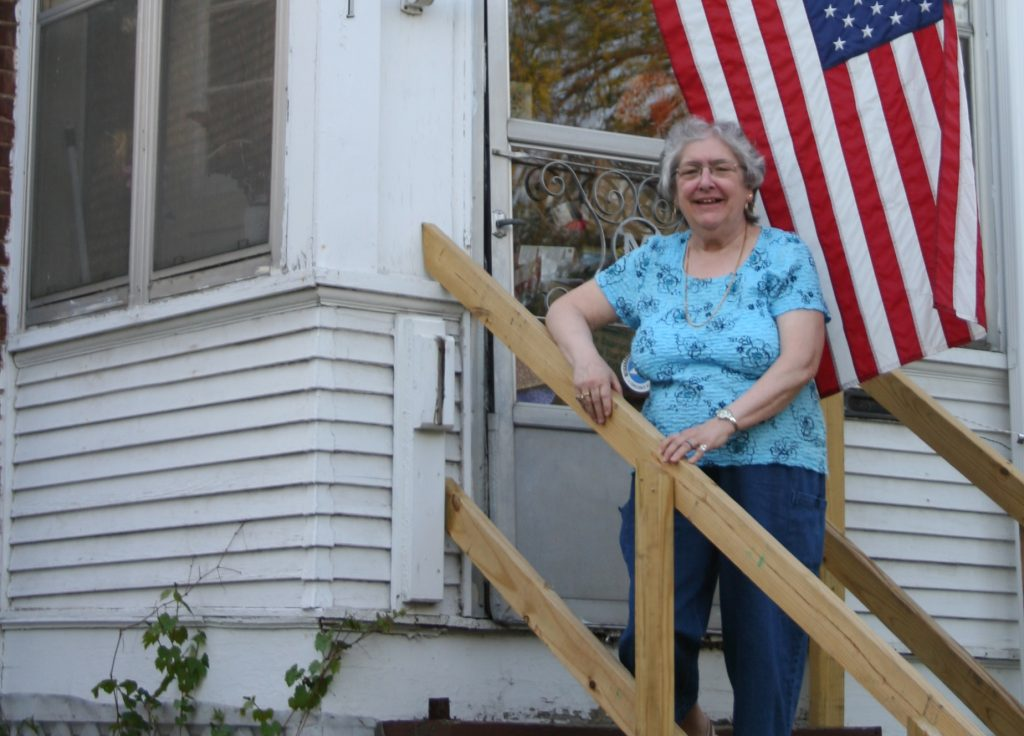 a home improvement customer stands on her new front steps.