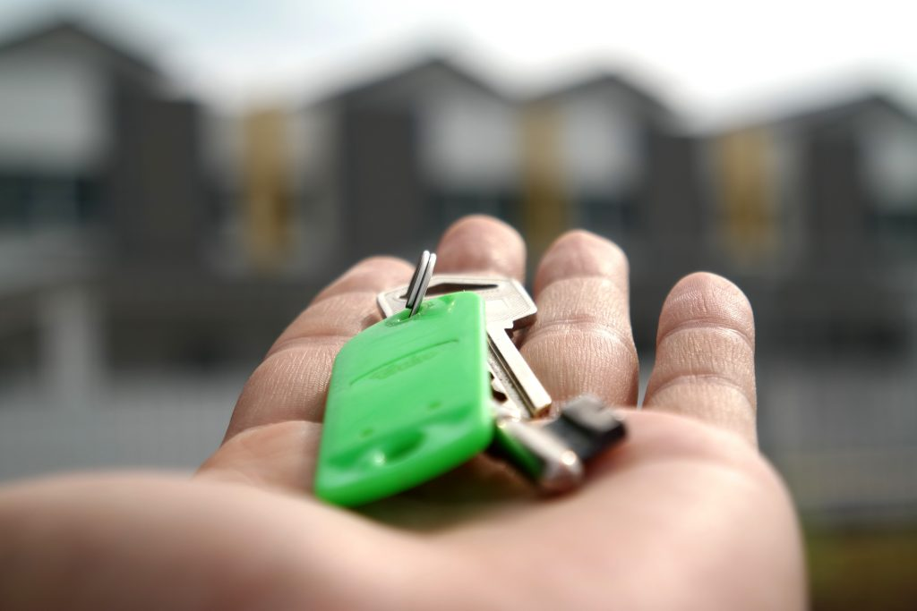 An outstretched hand holding a key ring with house keys. First mortgage programs make homeownership accessible.