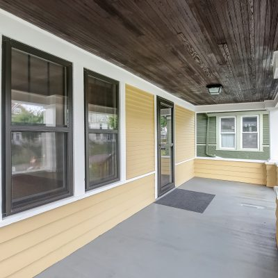 The front porch on a craftsman bungalow, preserved with original wood ceiling, cedar siding, and support columns.