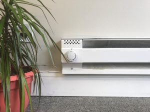 an electric baseboard heater and thermostat