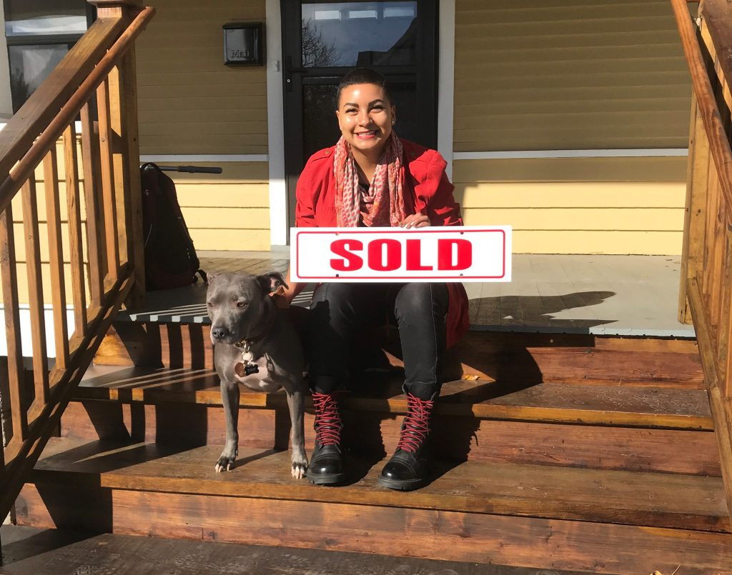 new homeowner and her dog sitting on the steps of their new home
