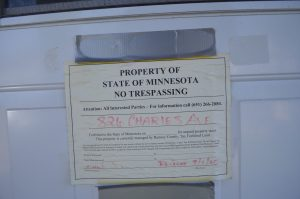 "A ""no trespassing"" sign posted on a vacant house."