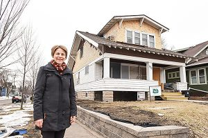 Becky Errigo stands in front of a house she renovated.