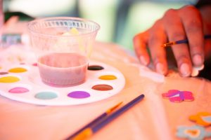 A close-up photo of the hand of a person painting a wooden flower cutout, and a paint palette with multiple vibrant colors.