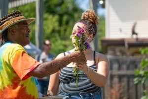 A man in a colorful tie-dye shirt receives a bouquet of purple flowers from a woman.