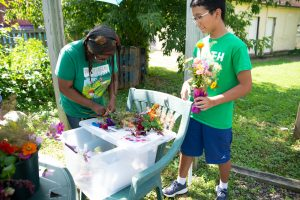 A volunteer helps a teen make a bouquet of zinnias and daisies