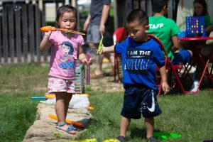 Two young children blow soap bubbles at a garden party at NeighborWorks