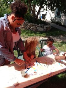 A woman and two young children paint wooden flower cutouts at a garden party