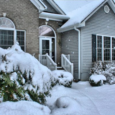 The front entrance of a one-story home pictured on a snowy day.