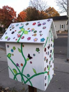 The back view of the Little Free Library at NeighborWorks Home Partners. The library has been painted white with green vines and leaves, and colorful flowers have been glued on the surface.