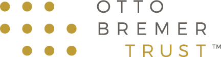 Logo for the Otto Bremer Trust. It shows a group of gold-colored dots on the left and the name of the trust on the right.