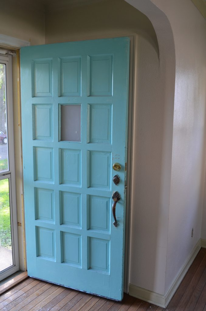 A turquoise-colored 15-panel door is the entrance to this 1940s colonial home.