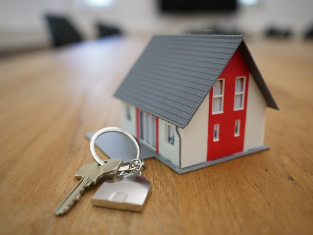 A model of a house and a keyring with a house key are photographed together on a table.