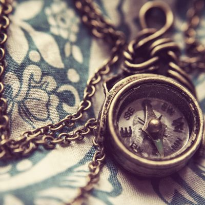 a vintage compass on a necklace chain is displayed on a floral patterned fabric
