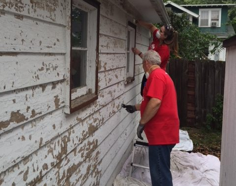 Two volunteers scrape paint from the side of a garage.