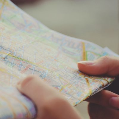 Two hands hold a folder paper map.
