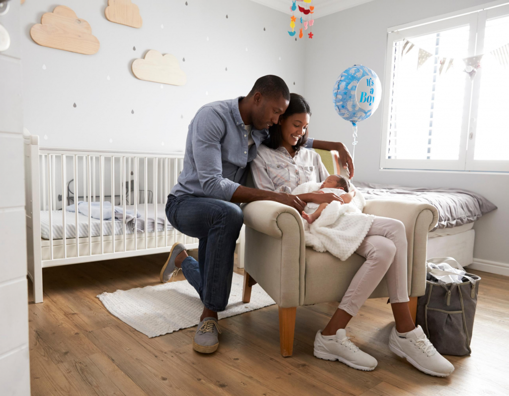 A Black couple embrace and smile at their newborn son in their home's nursery.