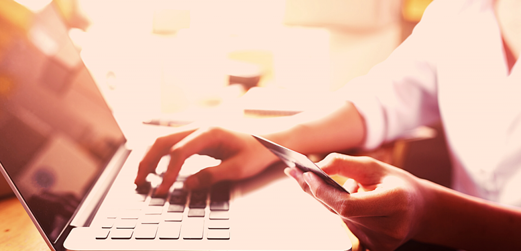 A person's hands are shown holding a credit card and typing on a laptop computer.