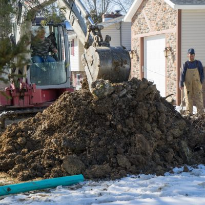 Two workers stand in the front yard of a home and observe as a third worker operates an excavator to dig a trench for installation of a sewer line.