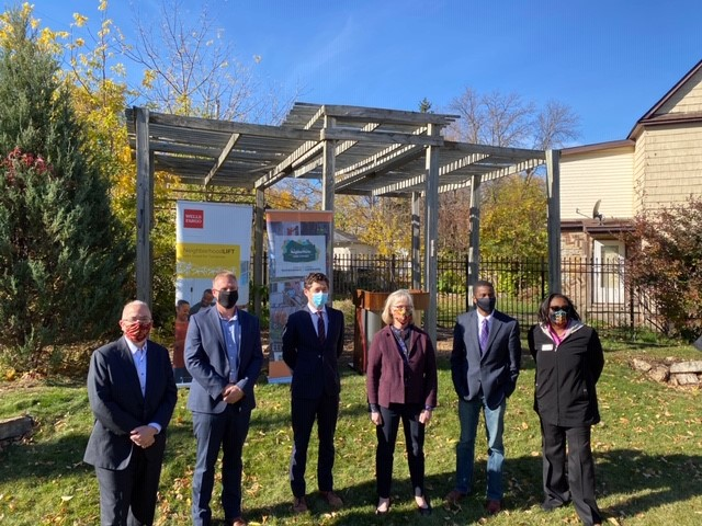 Six individuals, 4 men and two women, stand in front of a wooden pergola following a press announcment.