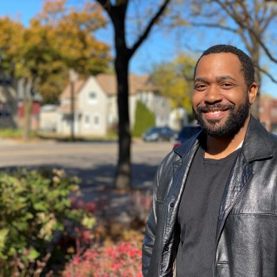 Juan Bates stands outdoors near his home on a fall day. Dale Street is in the background. He is wearing a black leather jacket and black t-shirt.
