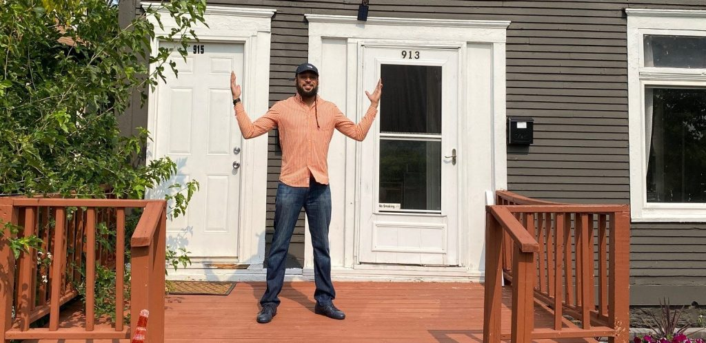 An African American man wearing an orange button down shirt, dark jeans, and a baseball cap stands on the deck of his new home with arms stretched to the side.