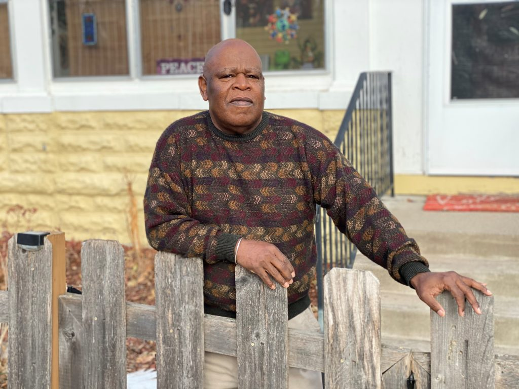 Robert, an older Black man, poses for a photo in front of his home. He is wearing a multi-colored sweater in golds and purples and has his hands placed on the fence in his front yard.