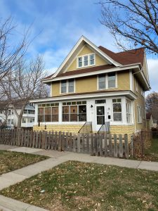 A 2.5 story home with an encolsed front porch is situated on a corner lot in Saint Paul. The siding is painted yellow with white trim and red-tone roof shingles.